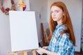 Beautiful woman painter standing near blank easel in art classroom