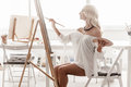 Beautiful woman paints on canvas