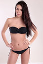 Beautiful woman with perfect body, with dark straight hair wears black bikini Royalty Free Stock Photo