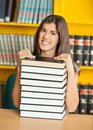 Beautiful woman with piled books smiling in portrait of while sitting university library Royalty Free Stock Photography