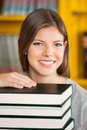 Beautiful woman with piled books smiling in portrait of young university library Royalty Free Stock Photography