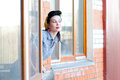Beautiful woman with pin up make up and hairstyle posing looking in window Royalty Free Stock Image