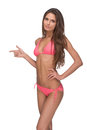 Beautiful woman in pink bikini attractive young looking at camera and pointing away while standing isolated on white Stock Photography