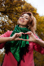 Beautiful woman in pink coat showing heart in the park autumn background Stock Photos
