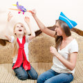 Beautiful woman playing airplane with child girl, having fun, happy smiling sitting on sofa Royalty Free Stock Photo
