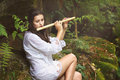 Beautiful woman playing flute after the rain in a forest romance and fantasy Royalty Free Stock Images