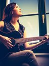 Beautiful woman playing guitar by the window Royalty Free Stock Photo