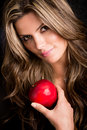 Beautiful woman portrait holding apple isolated over black Stock Photos