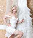 The beautiful woman portrait to the utmost bride in with a garter on a foot near a wedding dress Royalty Free Stock Photo