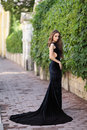 Beautiful woman portrait of a young in a black long dress on the street Royalty Free Stock Photo