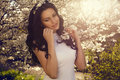 Beautiful woman posing at the spring blossom park smiling with black hair garden Royalty Free Stock Image