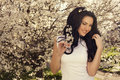 Beautiful woman posing at the spring blossom park smiling with black hair garden Stock Image