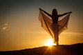 Beautiful woman posing at sunset on the beach the holding transparent skirt Stock Image