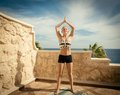 Beautiful woman practicing yoga outdoors against blue sky Stock Photo