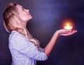 Beautiful woman praying side view of with candle in hands looking up on dark background about her dreams and wishes christmas Stock Photo