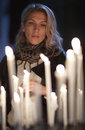 Beautiful woman prays, stands behind candles Stock Image