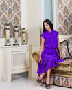 Beautiful woman in purple dress in luxury interior. Royalty Free Stock Photo