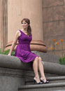 Beautiful woman in purple dress sitting on the steps Royalty Free Stock Photo