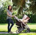 Beautiful woman pushing baby carriage in park portrait of young the Royalty Free Stock Image