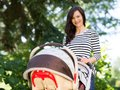 Beautiful woman pushing stroller in park portrait of young Stock Photography