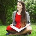 Beautiful young girl siting on the grass and reading a book edu
