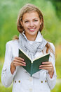 Beautiful woman reading green book young happy red against background of autumn park Stock Photos