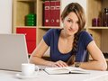 Beautiful woman reading and using a laptop photo of drinking coffee book at home or an office Stock Photo