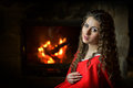 Beautiful woman with red cloak by the fire smiling sitting Royalty Free Stock Image