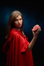 Beautiful woman with red cloak holding pomegranate in studio Royalty Free Stock Photos