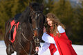 Beautiful woman with red cloak with horse outdoor in winter Stock Photo