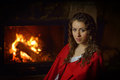 Beautiful woman with red cloak indoors sitting by the fire Royalty Free Stock Photos