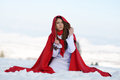 Beautiful woman with red cloak sitting on the snow in winter Royalty Free Stock Photos