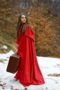 Beautiful woman with red cloak and suitcase outdoor in winter Royalty Free Stock Image