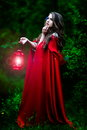 Beautiful woman with red cloak in the woods and lantern Royalty Free Stock Photos