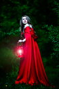 Beautiful woman with red cloak in the woods and lantern Royalty Free Stock Image