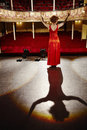 Beautiful woman in red gown on stage full length rear view of a standing floor Royalty Free Stock Photo