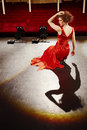 Beautiful woman in red gown on stage sensuous young sitting floor Stock Images