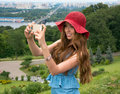 Beautiful woman in a red hat taken picture of herself selfie young with long hair photographed on the cell phone Stock Image