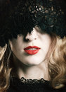 Beautiful woman with red lips and lace mask over her eyes Stock Photography