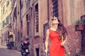 Beautiful woman in red summer dress walking smiling in Rome, Italy Royalty Free Stock Photo