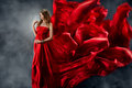 Beautiful woman in red waving silk as flame Royalty Free Stock Photo