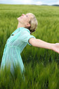 Beautiful woman rejoicing in the summer standing long fresh green grass countryside with her arms outstretched and head Royalty Free Stock Photos