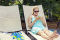 Beautiful woman relaxing and checking her cell phone a sitting in a lounge chair by the pool reading Stock Images