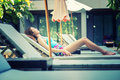 Beautiful woman relaxing on lounger near swimming pool in hotel, Royalty Free Stock Photo