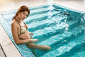 Beautiful woman relaxing at the luxury poolside. Girl at travel spa resort pool.