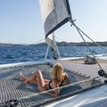 Beautiful woman relaxing on a summer sailing cruise, lying and sunbathing in hammock of luxury catamaran sailing around Royalty Free Stock Photo