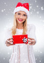 Beautiful woman with santa hat holding a small red gift box Royalty Free Stock Photo