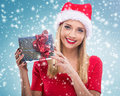 Beautiful woman with santa hat, holding two red gift box - snowfall Royalty Free Stock Photo
