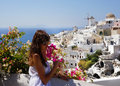Beautiful woman on santorini oia and flowers town view windmills Stock Photo
