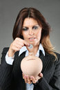 Beautiful woman saving money elegant and puts a coin in box conceptual Royalty Free Stock Image